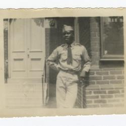 Soldier Leaning Against a Brick Building
