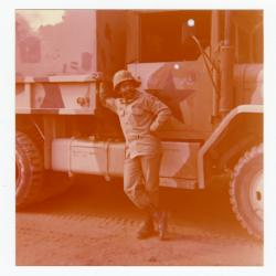 A military man leaning on a large vehicle