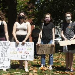 Four Young Adult Protesters with Signs